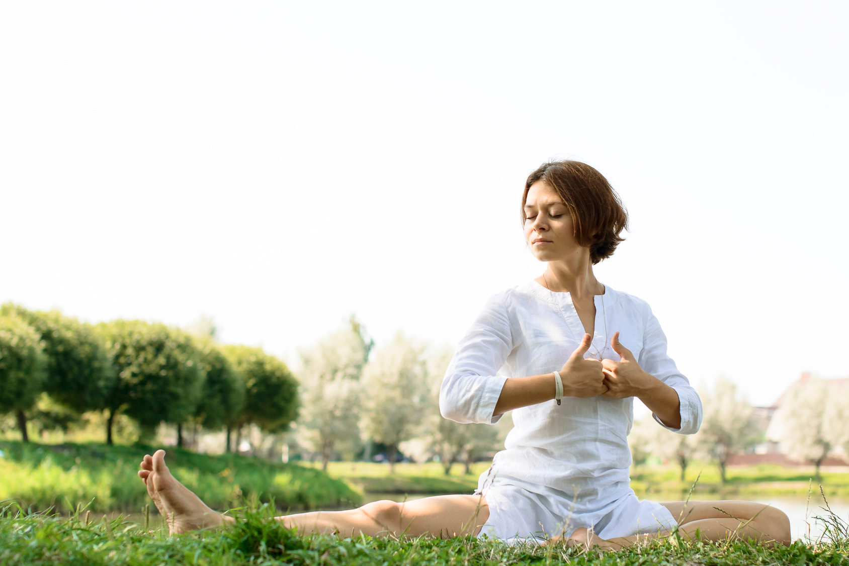 girl-in-white-clothes-practicing-yoga-at-the-river-bank